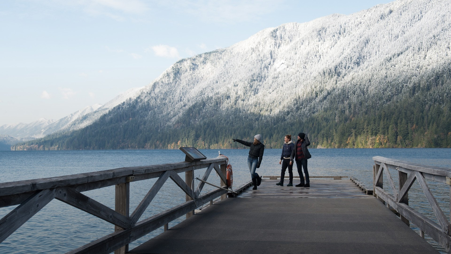 three people at the edge of a dock in front of lake and winter mountains