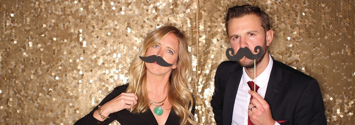 man and woman wearing fake moustaches at a party