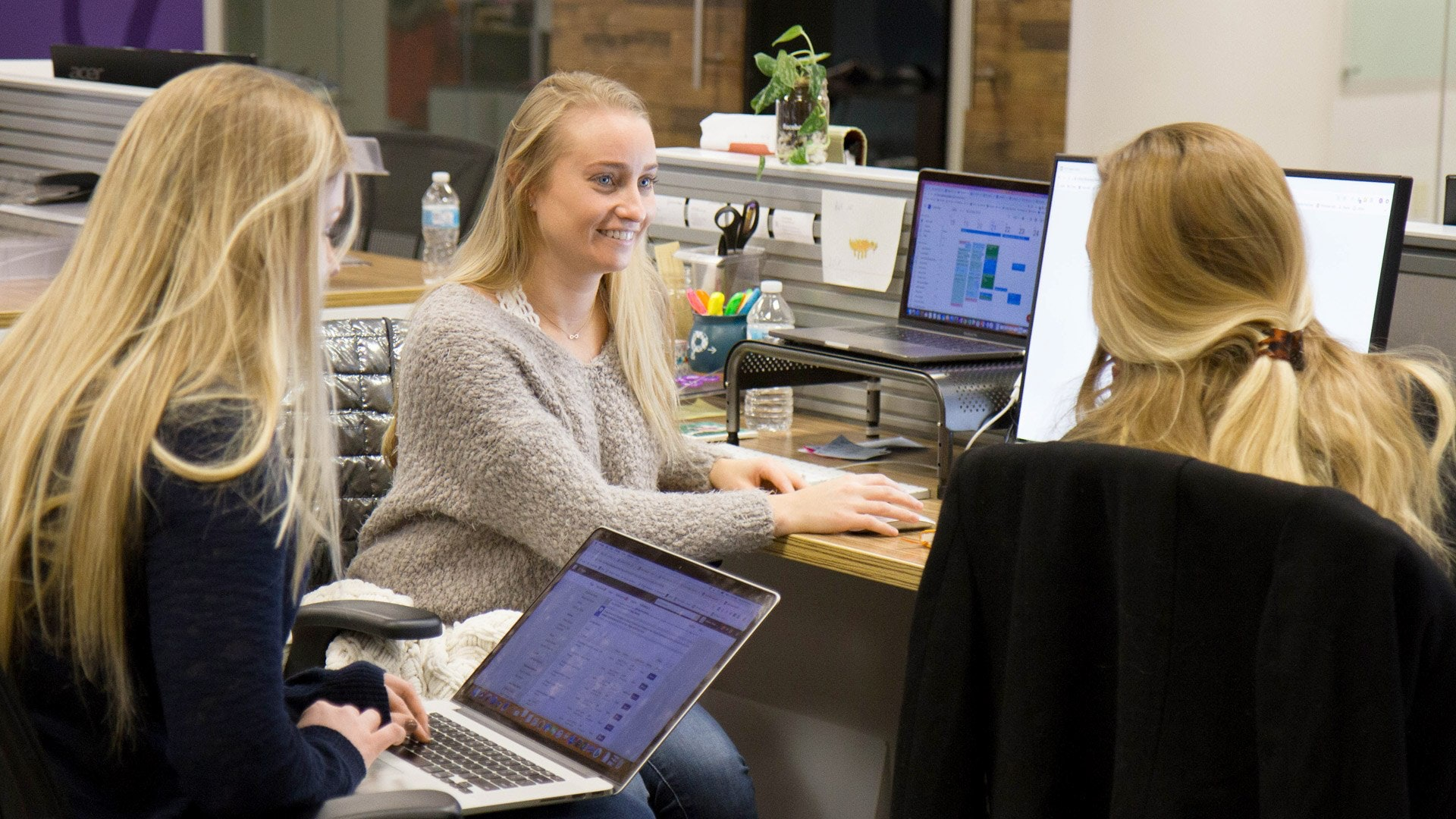 three digital marketers sitting in a modern office space