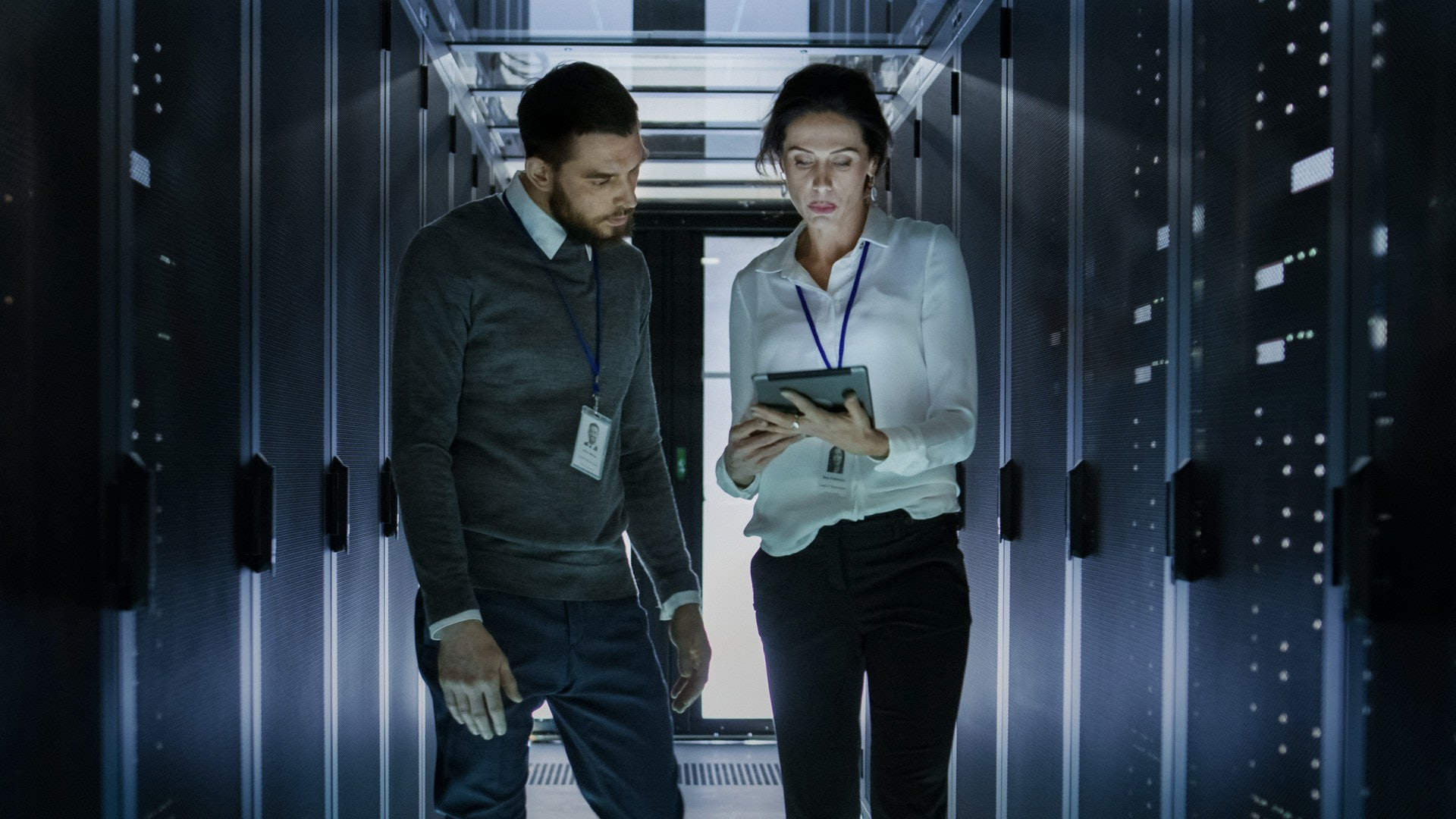 two technology workers walking through computer server room looking at an ipad