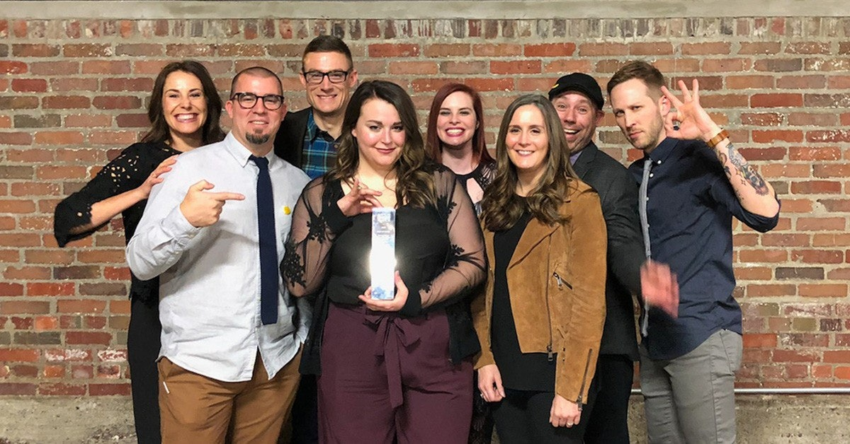 group of element three employees holding up addy award