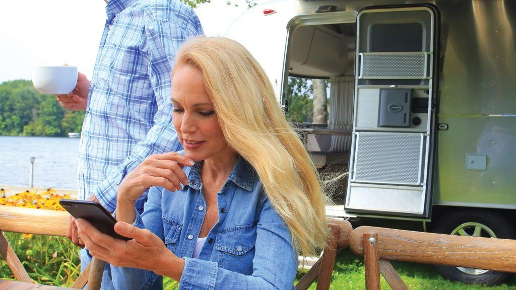 Woman at Picnic Table in Front of Airstream Looking at Marketing Materials on iPhone