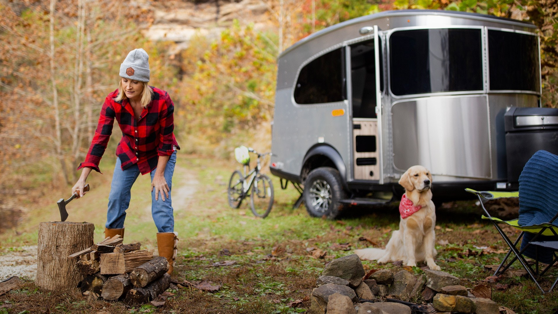 Woman and Dog Chopping Wood in Front of Airstream Basecamp