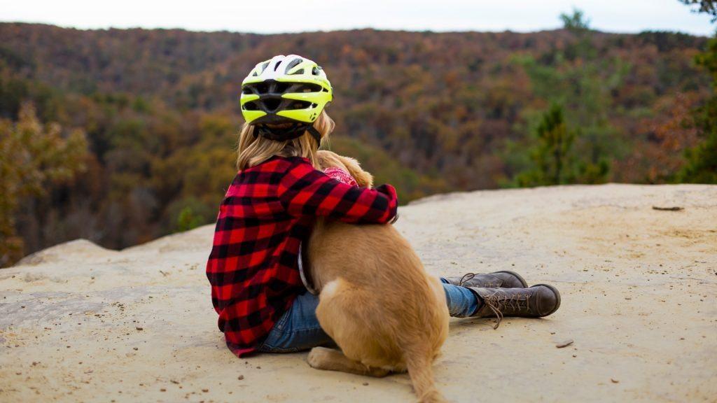Little Kid Hugging Golden Retriever Puppy Overlooking Woods