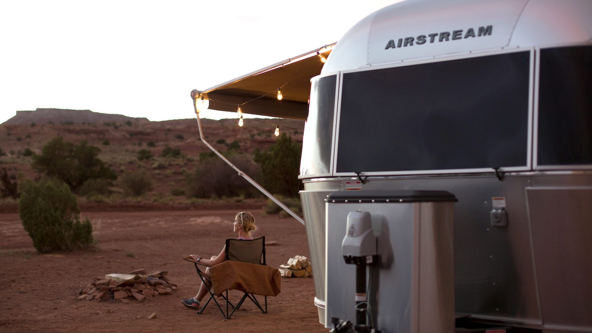Woman Sitting in Chair Outside Airstream in Desert