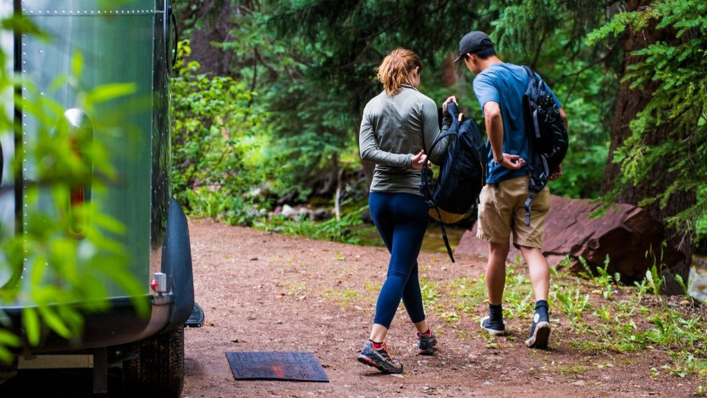 A Woman and Man Walking Out of Basecamp Travel Trailer into Forest