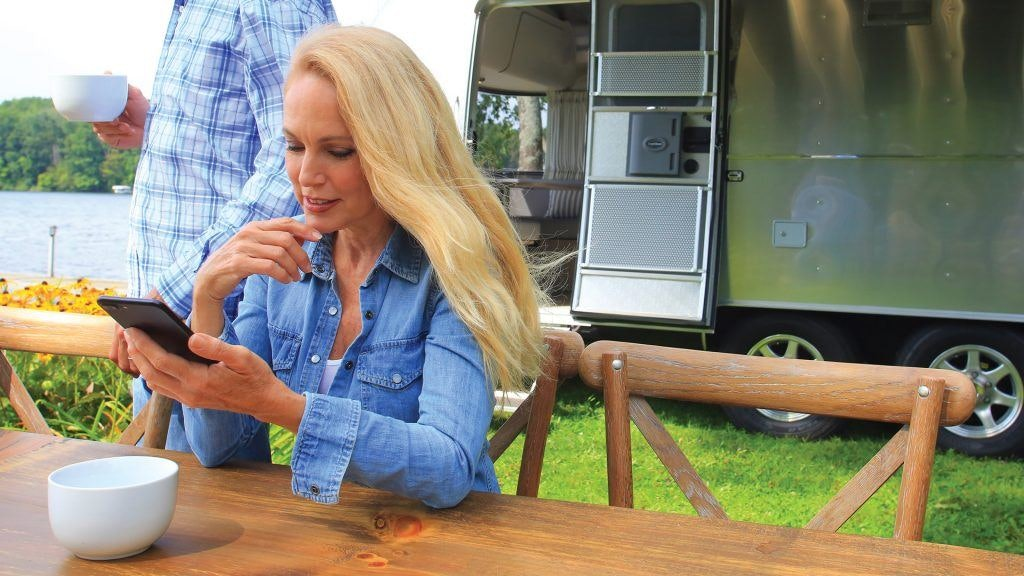 Baby Boomer Woman Looking at Smart Phone in Front of Airstream
