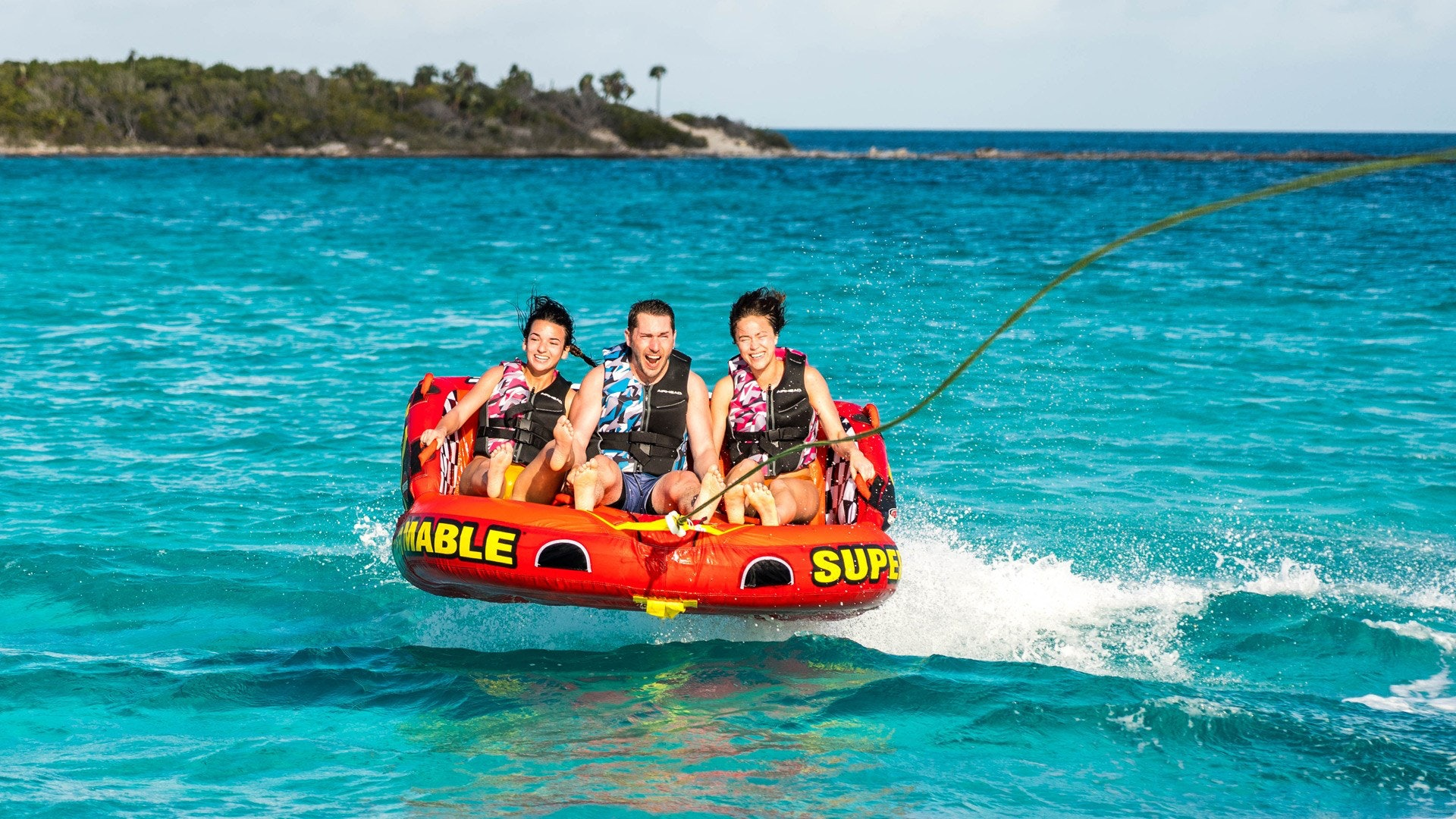 Three Teenagers Tubing on Airhead Tube